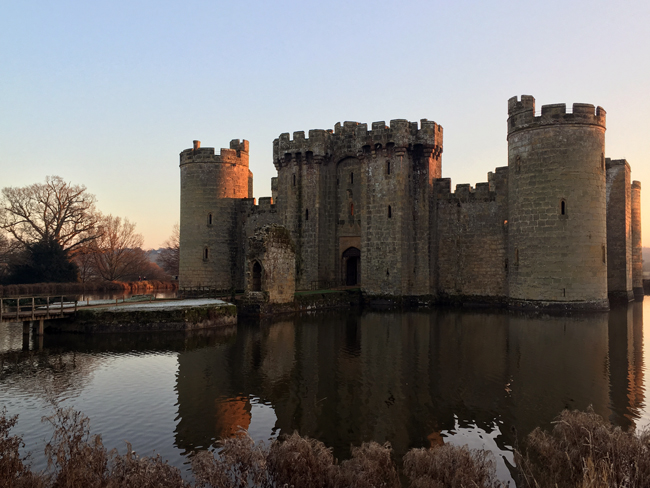 Sunset lowering over Bodium and its calm moat.
