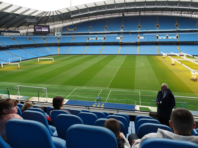 In the primo seats with the best view of Etihad Stadium.